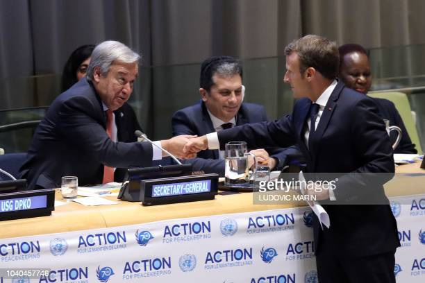 United Nations SecretaryGeneral Antonio Guterres shakes hands with French President Emmanuel Macron during the Action for peace event during the...