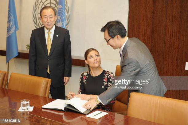 United Nations SecretaryGeneral Ban Kimoon looks on as Crown Princess Victoria of Sweden signs the UN guest book handed to her by UN Chief of...