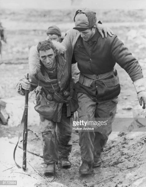 United Nations soldier in uniform helps a wounded Canadian rifleman to an aid station behind the front lines during the Korean War