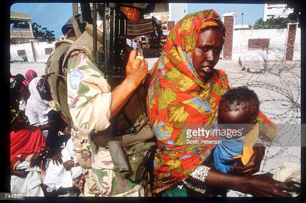United Nations soldier monitors a food distribution site while on a peacekeeping mission June 20 1993 in Mogadishu Somalia An estimated 350000...