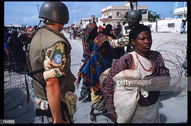 United Nations soldier stands among Somali people June 6 1993 in Mogadishu Somalia UN troops seized the residence of General Mohammad Aidid a warlord...