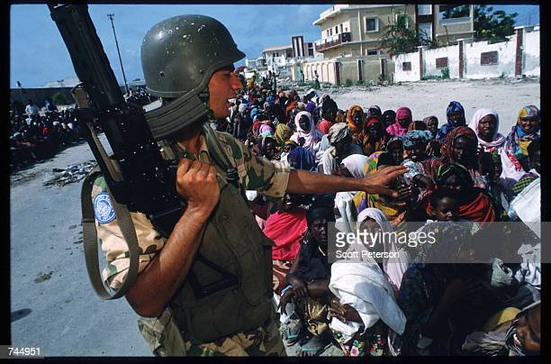 United Nations soldier stands over a group of Somali people June 6 1993 in Mogadishu Somalia UN troops seized the residence of General Mohammad Aidid...