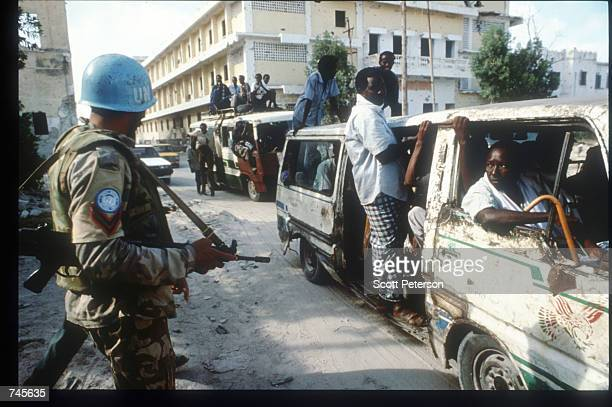 United Nations soldier watches protesters head towards a rally for General Mohammad Farrah Aidid October 14 1993 in Mogadishu Somalia A powerful...