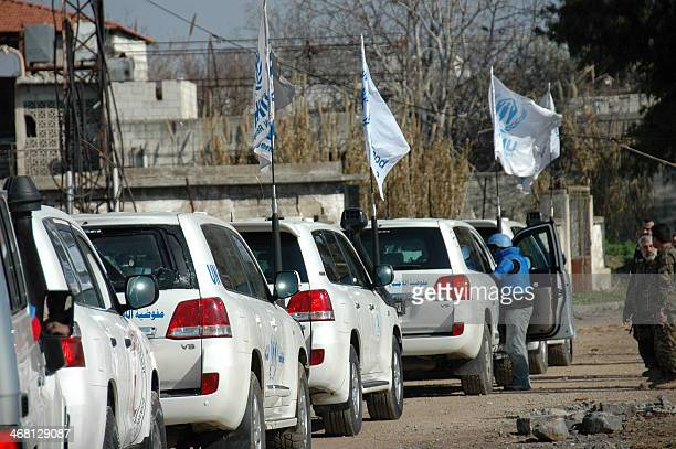 United Nations staff drive to the besieged district of the central Syrian city of Homs to help evacuate civilians to a safer location on February 9...