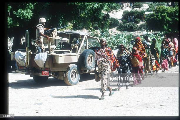 United Nations troops monitor a food distribution site while on a peacekeeping mission June 20 1993 in Mogadishu Somalia An estimated 350000 Somalis...