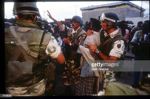United Nations troops restrain a crowd while on a peacekeeping mission June 20 1993 in Mogadishu Somalia An estimated 350000 Somalis died due to war...