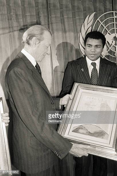 """United Nations- United Nations Secretary-General Kurt Waldheim accepts one of two """"paintings for peace"""" from and executed by world heavyweight boxing..."""
