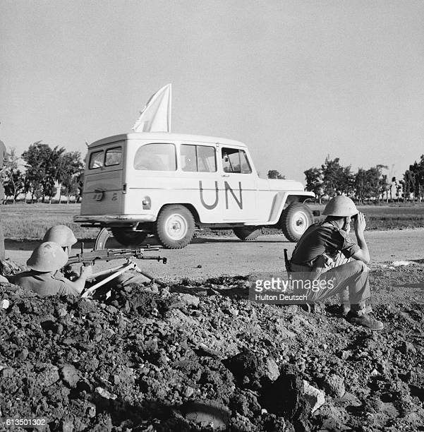 A United Nations vehicle bearing a white flag moves down the road while soldiers crouch nearby during the Suez Crisis in Egypt in 1956