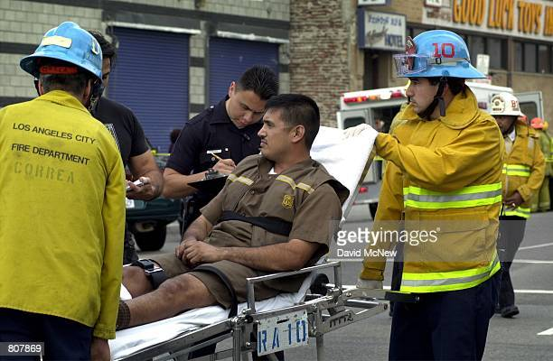 United Parcel Service driver is assisted by firemen after the crash of a Metropolitan Transit Authority bus that was hijacked by a gunman May 2 2001...