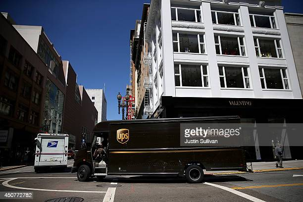 United Parcel Service drives through an intersection on June 17 2014 in San Francisco California UPS announced plans to begin to consider box size in...