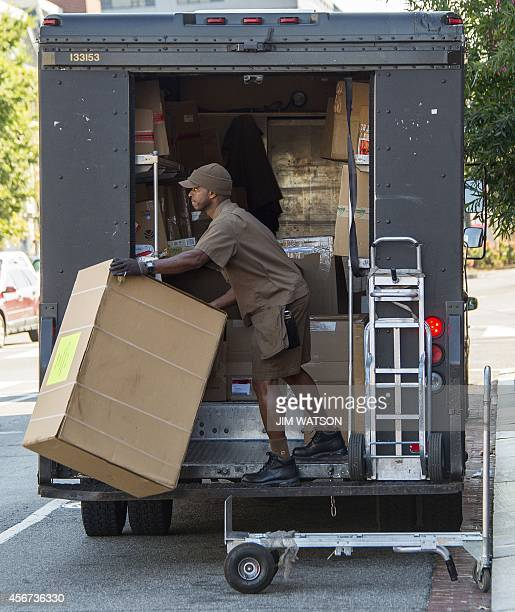 A United Parcel Service employee unloads his truck in Washington DC October 6 2014 AFP PHOTO / Jim WATSON