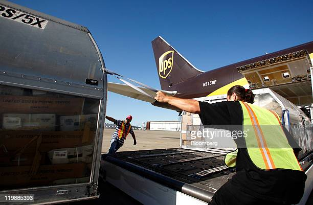 United Parcel Service Inc cargo loaders Eric Bautista left and Abel Gutierrez right load air containers onto a UPS Boeing 767 aircraft at the UPS air...