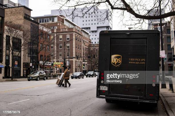 United Parcel Service Inc. Driver pushes a cart of packages across a street in Chicago, Illinois, U.S., on Monday, Nov. 30, 2020. Online shoppers in...