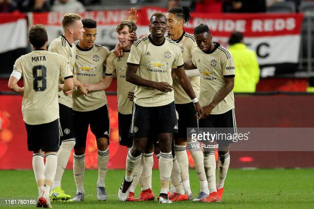 United players get a round James Garner of Manchester United after he scores a goal during the match between the Perth Glory and Manchester United at...