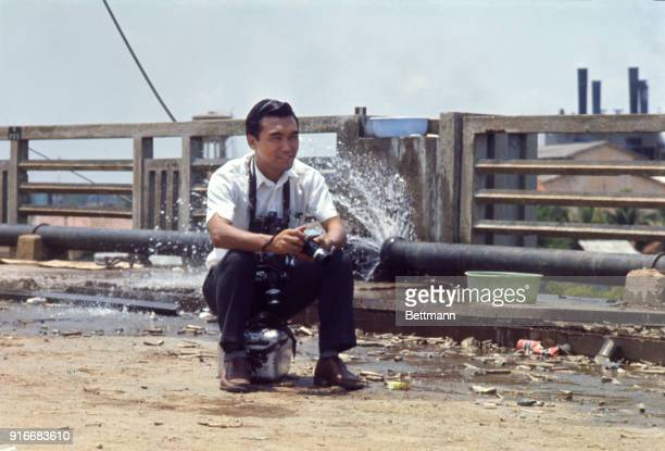 United Press International staff photographer Kyoichi Sawada pauses on 'Y' Bridge while covering recent action in the Cholon section of Saigon Water...
