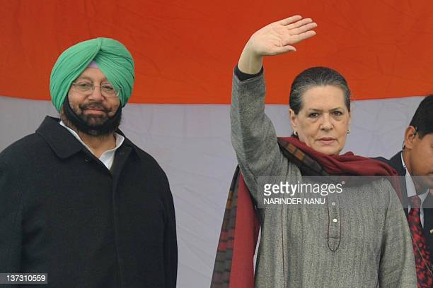 United Progressive Alliance government Chairperson and Congress Party President Sonia Gandhi waves to supporters next to former Chief Minister of...
