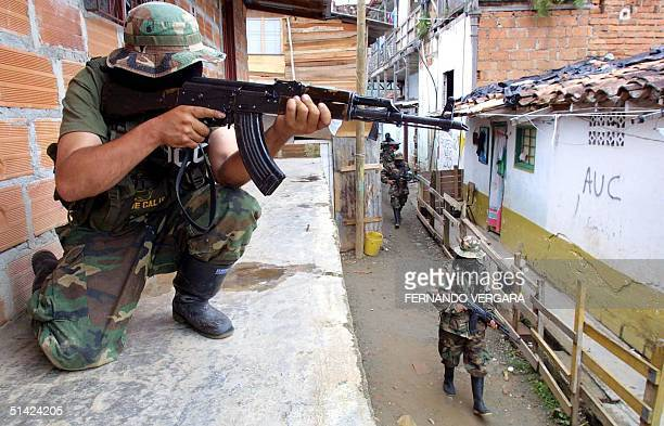 United Self Defense Force soldier patrols a walkway in the barrio San Javier in the city of Medellin Colombia 08 July 2002 as the AUC continues to...