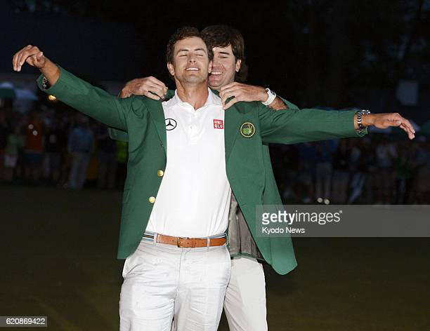 AUGUSTA United States Adam Scott of Australia has a green jacket put on by Bubba Watson of the United States the winner of the 2012 Masters...