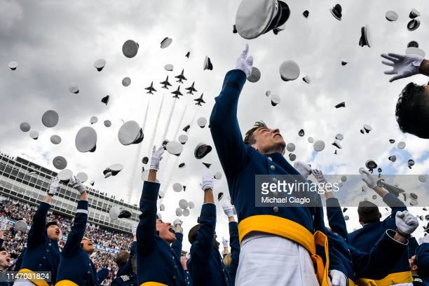 United States Air Force Academy cadets throw their hats in the air as a team of F16 Air Force Thunderbirds fly over the Falcon Stadium as they...
