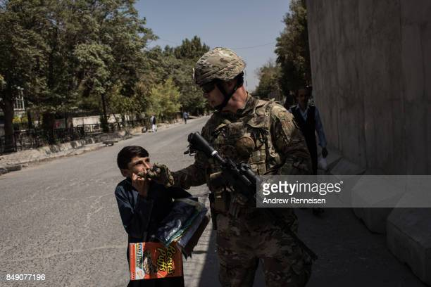 United States Air Force Major John Ross greets a local Afghan on the way to a public affairs advising mission with the Afghan Ministry of Defense on...