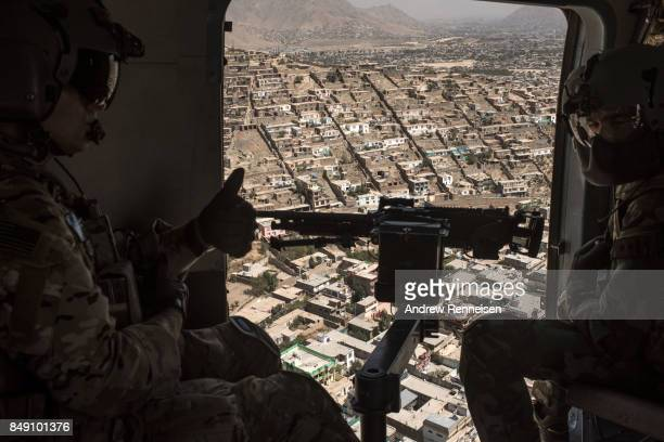 United States Army advisor for the Afghan Air Force 777 Special Mission Wing signals the Afghan crew chief during a training mission on September 13...