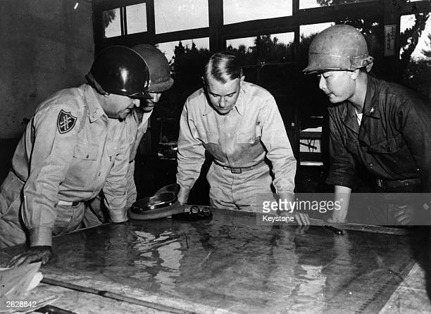 United States Army Chief of Staff General Collins studying a map of the front line during the battle for Korea, with Lieutenant General Walker,...