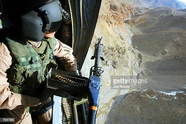 United States Army door gunner Sgt Jeff Bierman from Alton Illinois flies March 17 2002 over eastern Afghanistan in a Chinook helicopter The...