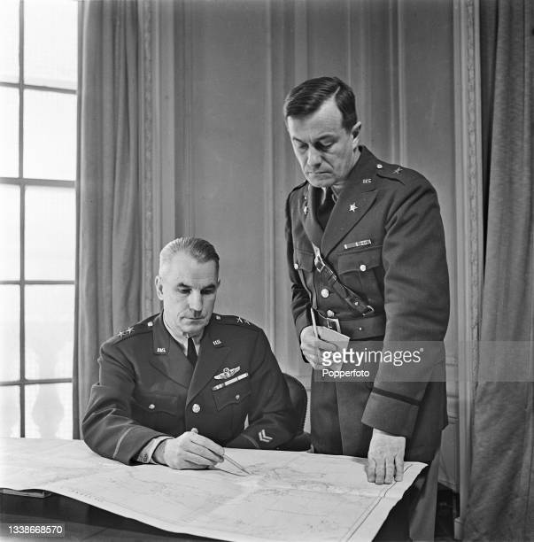 United States Army officer Major General James Eucene Chaney , Head of the Special Army Observers Group, seated at a desk studying a map with, on...