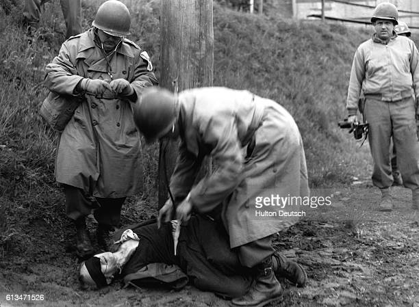 United States Army physicians examine the body of Richard Jarczyk to be sure that he is dead after execution by a firing squad in Germany in 1945...