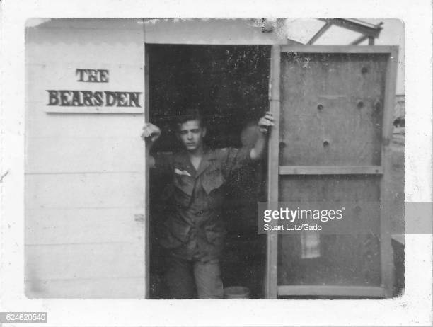 A United States Army serviceman in uniform standing in the doorway of a wooden building there is a sign on the exterior of the building that reads...