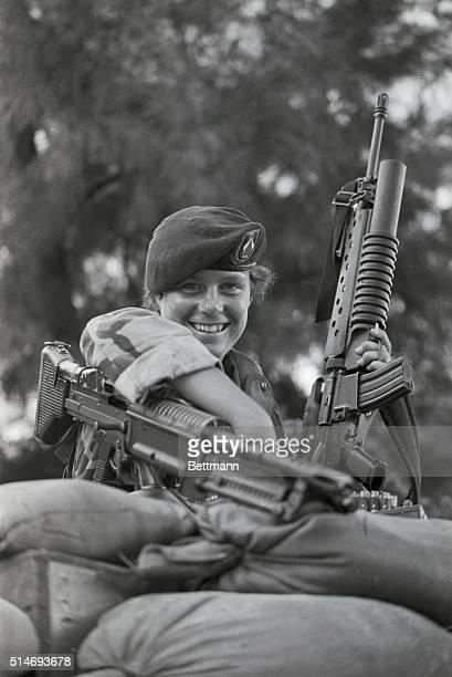 United States Army soldier Elizabeth Milliken rests with her machine guns behind a sandbag barrier during the Grenada invasion of 1983 | Location...