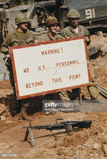 United States Army troops of the 591st Engineer Company hold up a sign stating 'Warning No US Personnel Beyond This Point' on the border between...