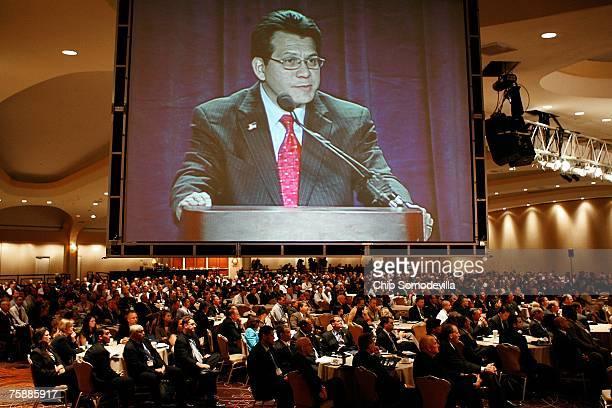 United States Attorney General Alberto R Gonzales appears on a large television screen while delivering remarks about the Justice Department's...