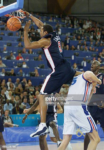 United States basketball player Vince Carter jams the ball over France's Frederic Weis during the second period of their men's preliminaries...