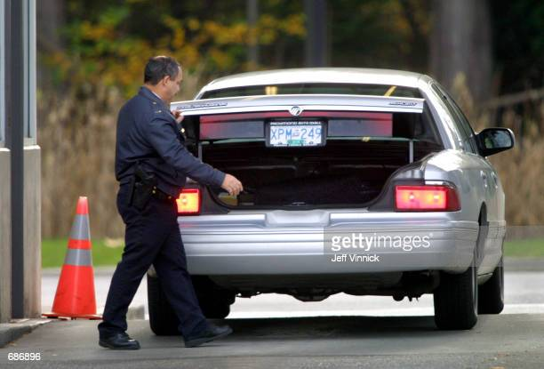 United States border guard inspects a vehicle from Washington State at the border crossing between Point Roberts Washington and Tswassen British...