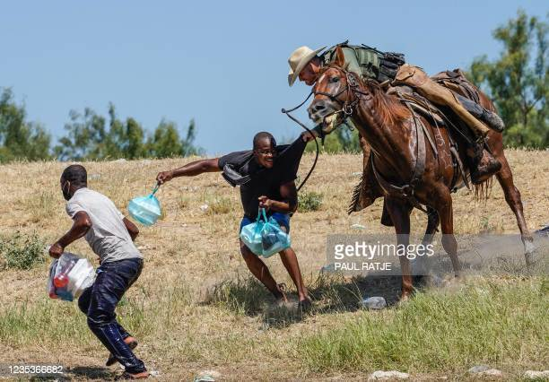 United States Border Patrol agent on horseback tries to stop a Haitian migrant from entering an encampment on the banks of the Rio Grande near the...