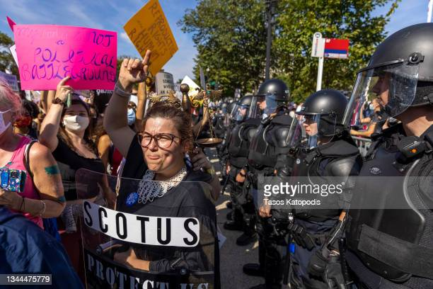 United States Capitol Police in riot gear stand between Women rights activists and anti-abortion activist, as they gather in front of the supreme...