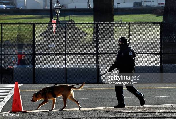 United States Capitol Police officer with a dog walks the perimeter of the U.S. Capitol grounds in the early morning near First Street, N.W., and...