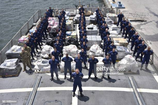 United States Coast Guard crew standing with $390 million in confiscated cocaine and marijuana from Mexican and Central American smugglers, at sea,...