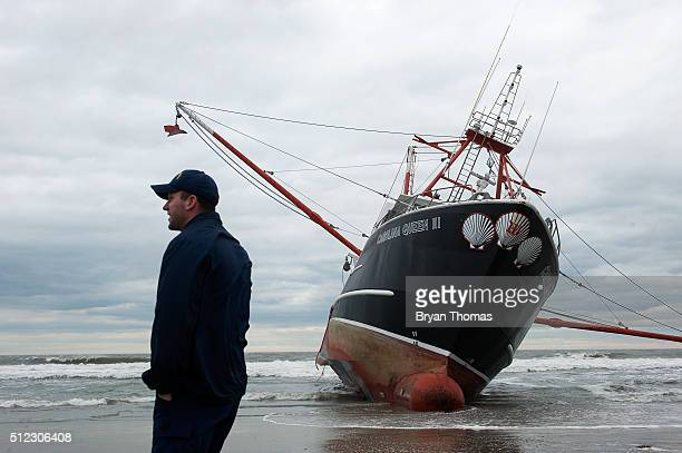 United States Coast Guard member stands in front of an aground fishing vessel on the shore of Rockaway Beach on February 25 2016 in Queens NY The...