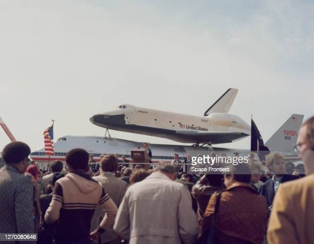 United States Congressman Ronnie Flippo addresses a crowd from a lectern with the Space Shuttle Enterprise atop NASA 905, a 747 carrier aircraft in...