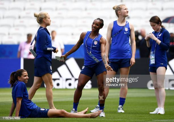 United States' defender Crystal Dunn , flanked by her teammates, dances in the pitch during a training for the France 2019 Women's World Cup at the...