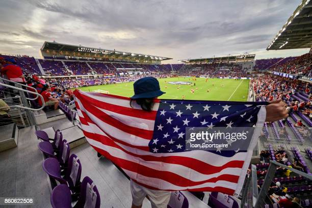 United States fan holds up and spreads a United States flag in celebration during the World Cup Qualifying match between the the United States and...
