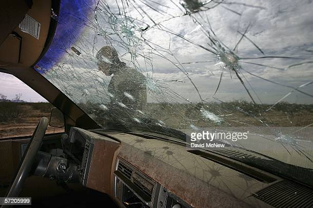United States Fish and Wildlife Service officer Jeremy Bucher is seen through the broken windshield of a vehicle that had been illegally driven...