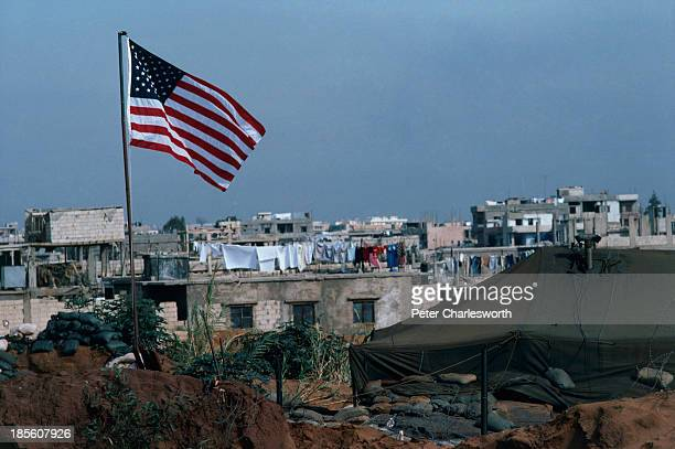 United States flag flies above a US Marines' fortified position inside Beirut's international airport with Beirut's southern suburbs in the...