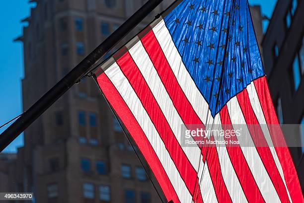 United States flag or US flag also known as the American flag in downtown New York city The national symbol is in bright light surrounded by dark...