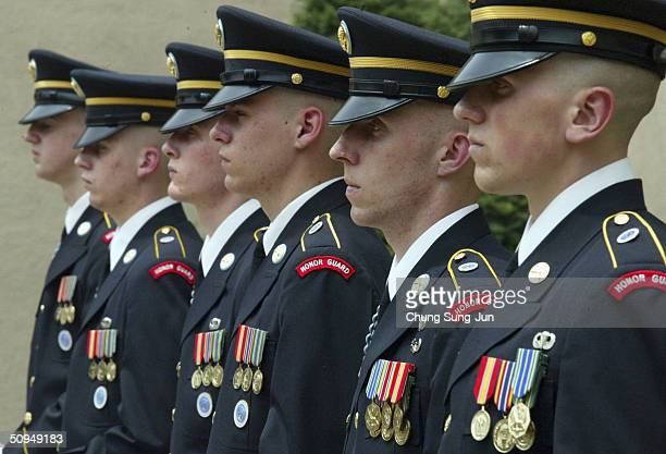 United States Forces Korea honor guard on stand to attention at a service for late US President Ronald Reagan in a chapel at a US army base on June...