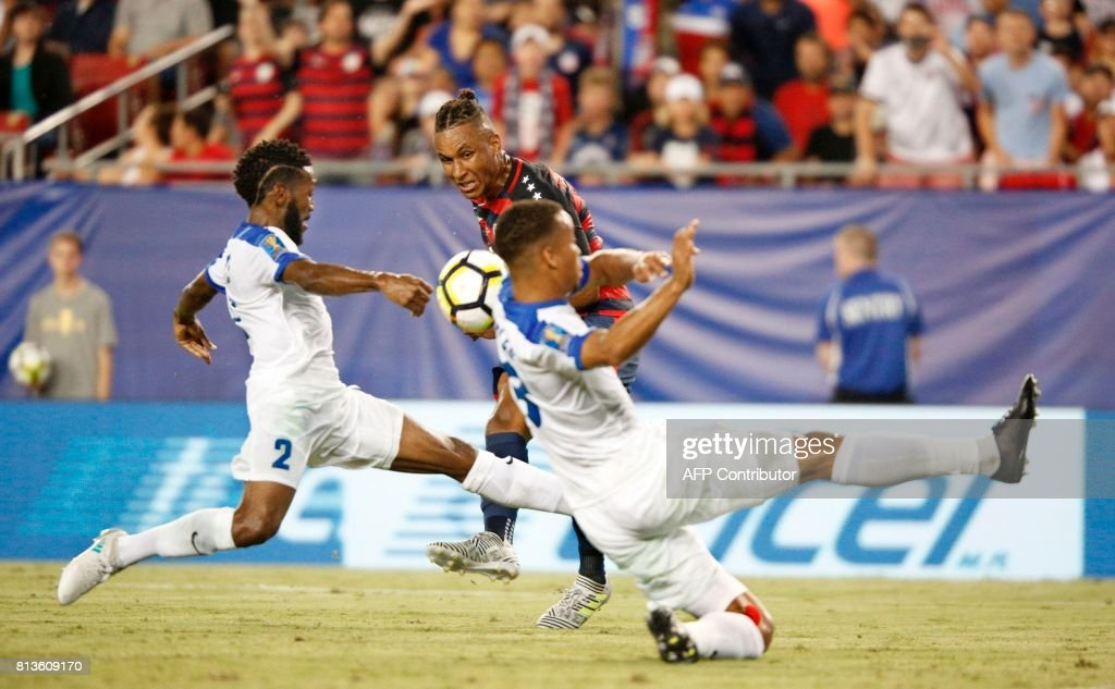 United States forward Juan Agudelko (C) tries to squeeze a shot on goal between defenders Nicolas Zaire (L) and Jordy Deelem of Martinique during their Group B Gold Cup soccer game on July 12, 2017 at Raymond James Stadium in Tampa, Florida. The US beat Martinique 3-2. / AFP PHOTO / Gregg Newton / Gregg Newton