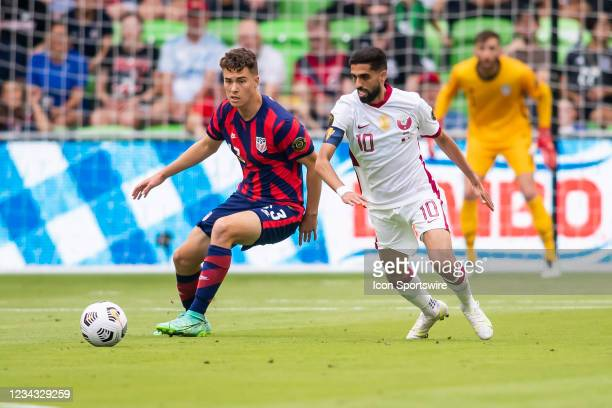 United States forward Matthew Hoppe and Qatar forward Hassan Al Haydos chase down a loose ball during the Gold Cup semifinal match between the United...