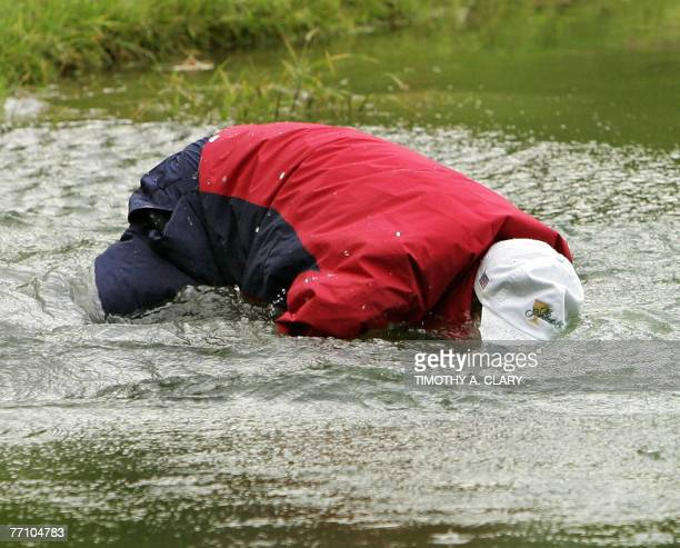 United States golfer Woody Austin falls after hitting out of the water on the 14th hole during the Four-Ball Matches of The Presidents Cup 28...